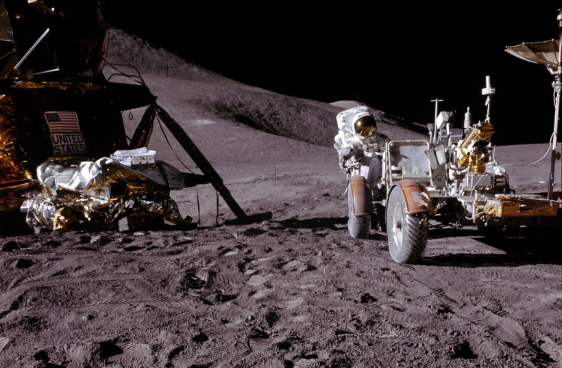 The lander to the left of the image with the rover to the right. An astronaut looks toward the camera from behind the rover.