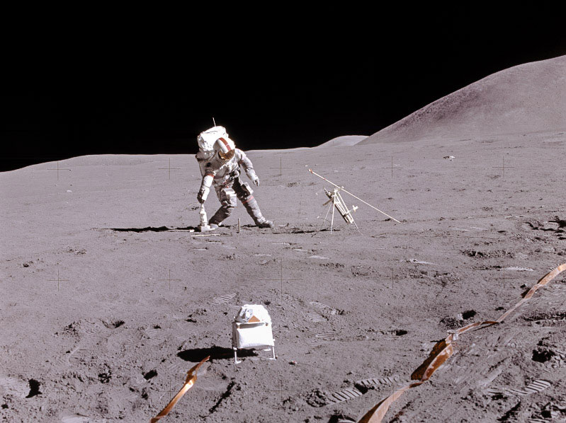 An astronaut on the lunar surface faces the camera and leans to the side to pick up a tool.