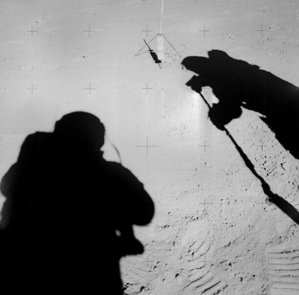 The shadows of two astronauts, one to the left and right, seem to be facing one another
