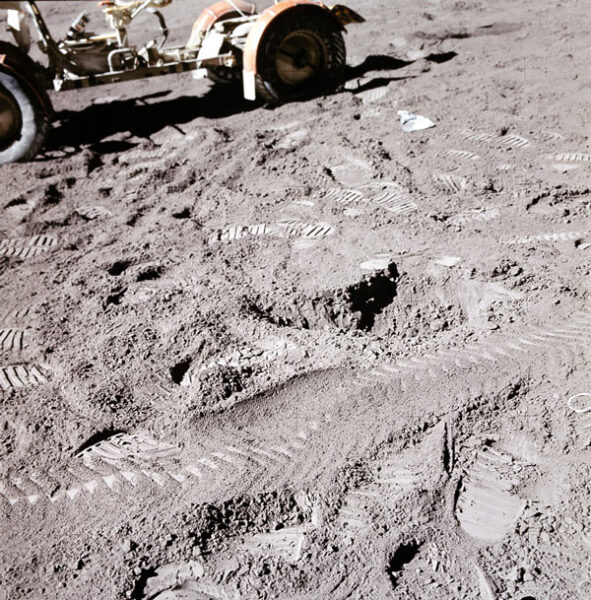 With the rover in the background, the lunar soil is shown with many boot prints and rover tracks. The rover tracks appear to be less deep.