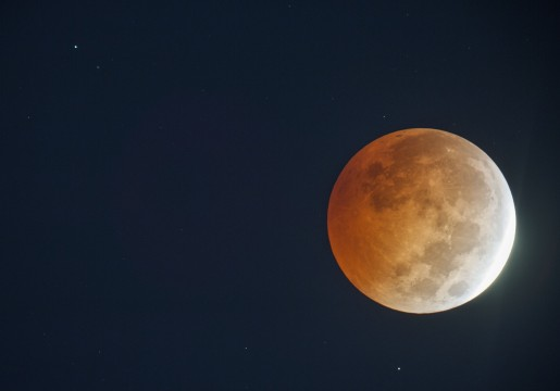 The planet Uranus appears as a starlike object at upper left as it hangs close to the eclipsed moon in this photo made through an 8-inch reflecting telescope at 6:21 a.m. Wednesday morning October 8, 2014.