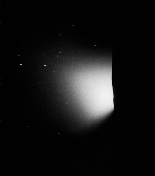 a burst of light appears in the center of the image, reflecting off of dust, over the lunar horizon to the right