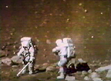 Two astronauts in the foreground appear to be standing at a boundary of rocks.