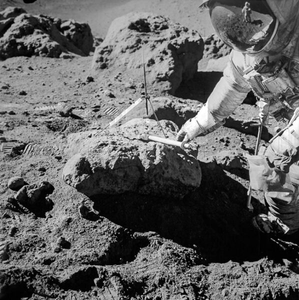 One astronaut leans over a rock and tools while another is reflected in his visor.