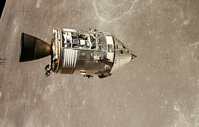 The command module centered orbiting over the lunar surface, cylindrical in shape with a pointed nose.