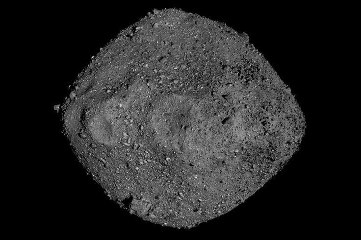 A diamond-shaped grey asteroid with ridges, holes, and craters in it, against a black background