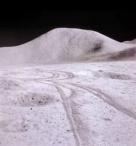 The lunar surface with rover trails and a hill in the background, which stands out drastically against the black background of space.