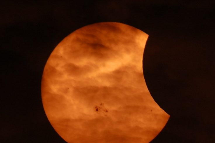 Image of partial solar eclipse as seen through clouds