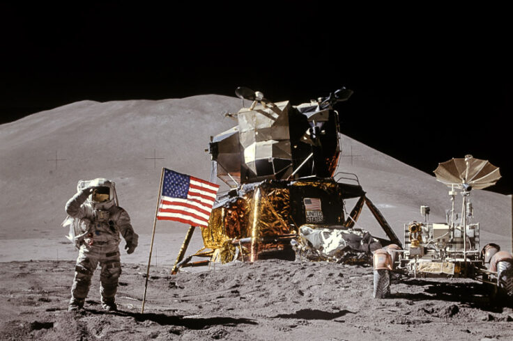 Astronaut stands to the left of American flag on the lunar surface, with hills in the background