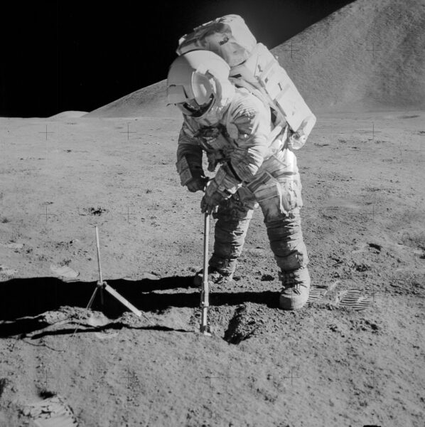 astronaut places tool into ground on lunar surface