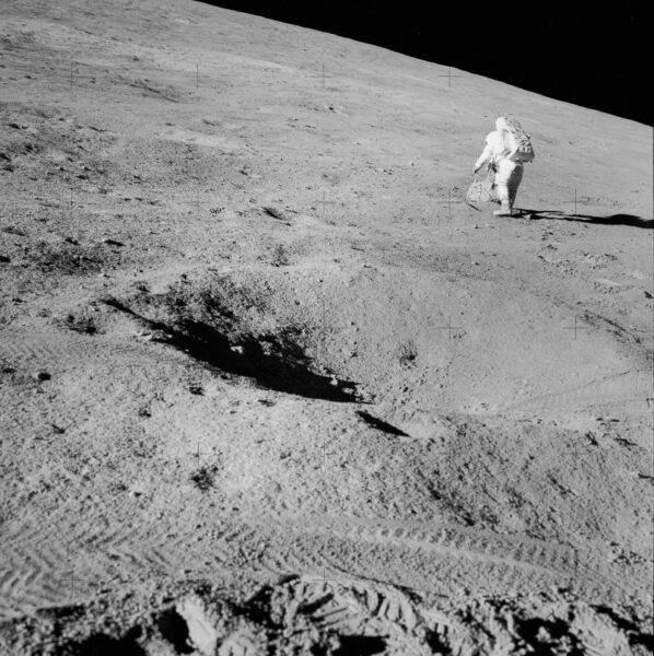 an astronaut walked the lunar surface in the distance, with a crater in the foreground