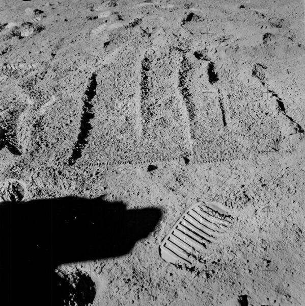 the imprints of a rake used to gather rocks from the lunar soil, next to an astronaut's footprint