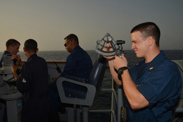 A U.S. Navy officer uses a sextant at sea.