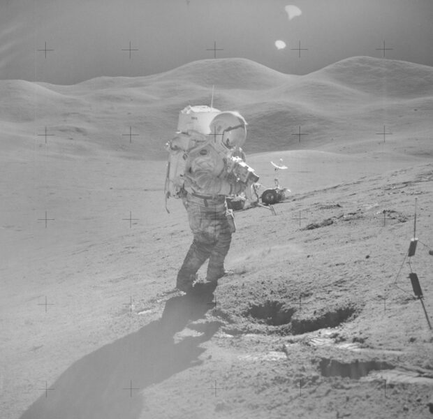 A bright glare shown as an astronaut walks the lunar surface with the sun visor down on his suit