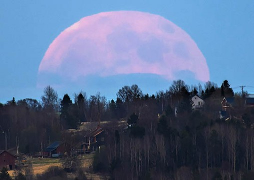 The Moon looms huge in this telephoto view taken of moonrise over the Swedish village Marieby in June 2014. Göran Strand