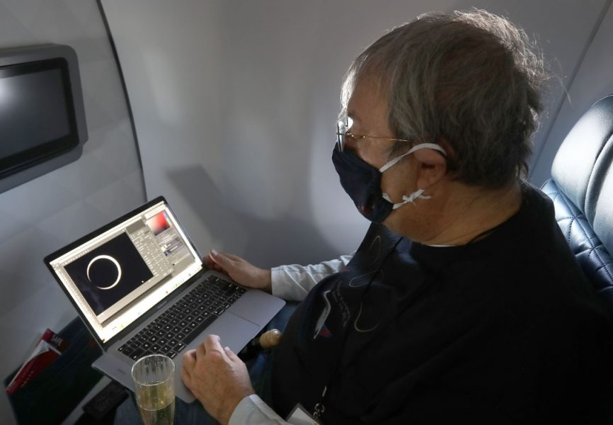 a man sits on a plane with a laptop in his lap, looking at an image of a solar eclipse