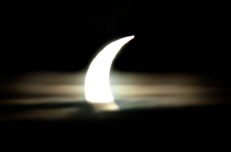 Partial solar eclipse above clouds