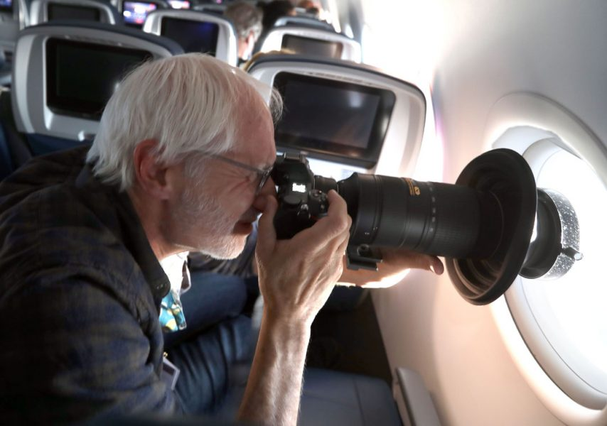 a man holds his camera up to the window inside a plane
