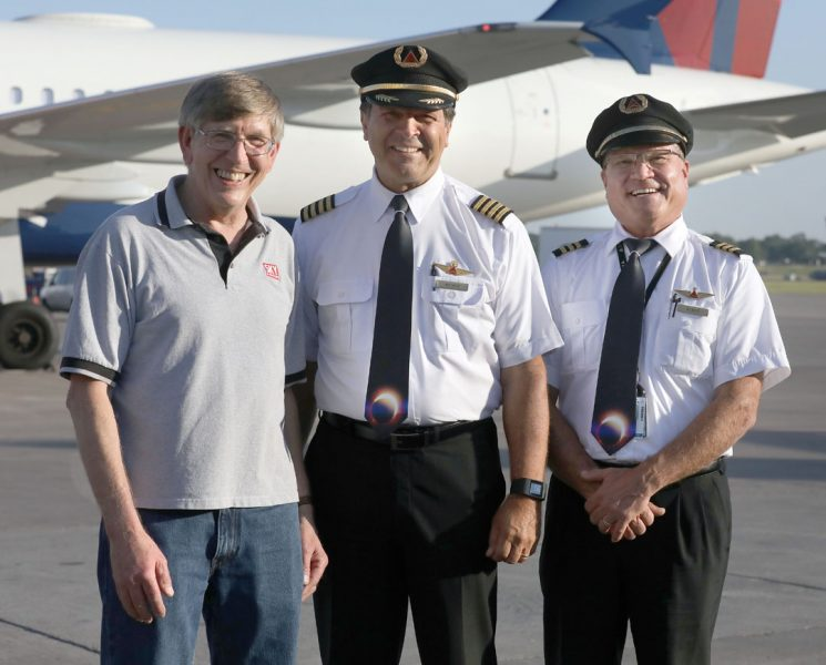 three men - two in pilot's uniforms and one in plain clothes - stand in front of an airplane, smiling