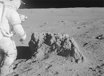 Apollo 14 astronaut checks out a lunar rock