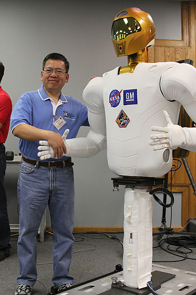 Edwin Aguirre shakes hands with Robonaut 2