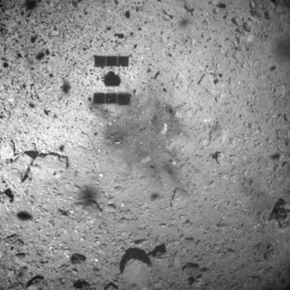 a close up of the asteroid's surface with the faint shadow of a spacecraft over it, in greyscale