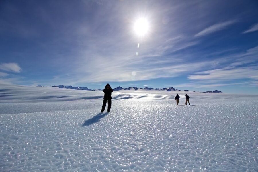 people stand on a iceberg under a bright sun