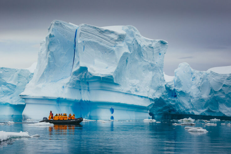 people in a small boat pass in front of a large iceberg