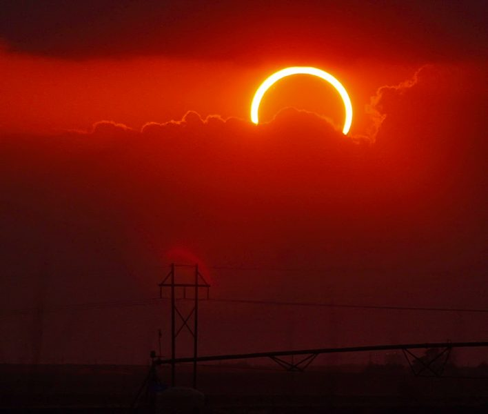 a ring of fire eclipse above red clouds