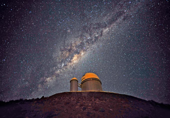 The ESO 3.6-metre telescope at La Silla, during observations. Across the plan of the picture, is the Milky Way, our own galaxy, a disk-shaped structure seen perfectly edge-on.