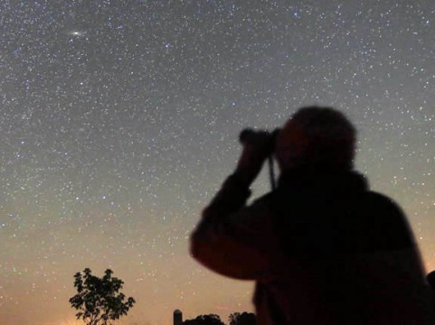 Amateur astronomer Annmarie Geniusz of Duluth, Minnesota, examines M31, the Andromeda Galaxy through 7x50 binoculars on a recent clear night.