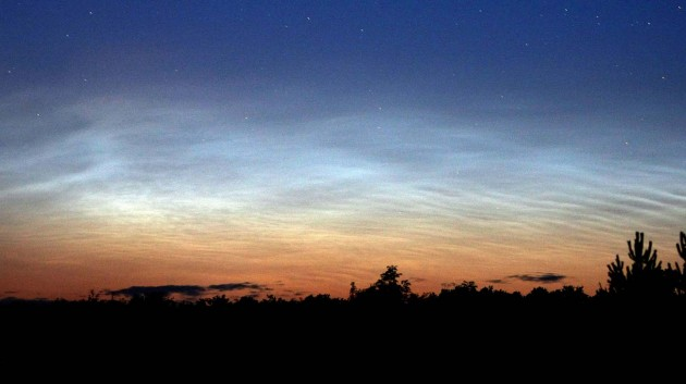 Striking noctilucent cloud display on July 31, 2008. Look for blue-colored swirls, eddies, and ripples very low in the northern sky. Credit: Bob King