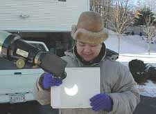 Sky & Telescope image archivist Imelda Joson shows how to safely view a partial eclipse of the Sun on Christmas day, 2000. She demonstrates the projection method of solar viewing by projecting the eyepiece image onto a white card.