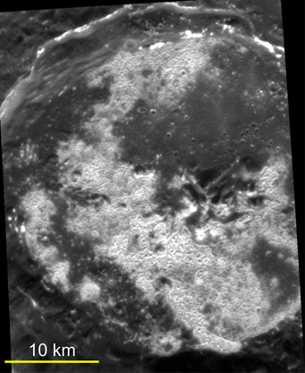 "The high-resolution, targeted image of Sander crater reveals that the bright portions of the floor consist of large numbers of shallow irregular depressions (""hollows""), giving an etched appearance to the surface."