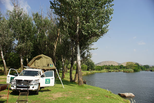 Camping at the shore of the Vaal River, close to the center of the 300-kilometer Vredefort impact crater. The granite hills in the distance are part of the crater's central ring structure.