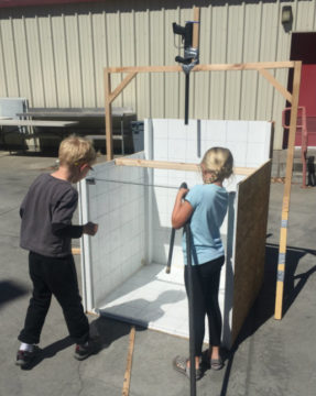 Picture of kids filling water tank for paintball experiments