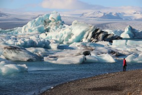 Icebergs calved off a distant glacier dwarf a visitor at the Jökulsarlon lagoon.