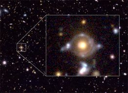 Eye of Horus in pseudo color. Enlarged image to the right. The yellow object at the center is a galaxy about 7 billion light-years away and bends the light from two background galaxies. NAOJ