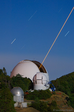 © 2006 Laurie Hatch / image and text - LICK OBSERVATORY - Mt. Hamilton  California 2006 July 8 - AUTOMATED PLANET FINDER TELESCOPE - Two of the most advanced technologies in astronomy are represented in this two-minute  digital time exposure. In this view looking east from Observatory Peak,  a 12-watt yellow  sodium laser emanates from the Shane 3-meter Reflector dome, located on Tycho Brahe Peak. It  is a component in the worldÕs first scientifically successful and highly specialized Laser  Guide Star Adaptive Optics system. This technology enables astronomers to reduce the effects  of atmospheric distortion, yielding celestial data so improved that they rival those of  space-based telescopes. With a telescope mirror only slightly smaller than the Shane 3-meter,  the newly constructed and more efficient 2.4-meter Automated Planet Finder dome is located  directly in front of the Shane. Fully robotic and equipped with a high-resolution spectrograph  optimized for precision Doppler measurements, it will enable off-site astronomers to detect  rocky planets of Earth-size masses within our local galactic neighborhood. On Huygens Peak at  foreground left, the silver dome of the 0.6-meter Tauchmann Reflector reveals the brilliant  light of a waxing gibbous moon. Note the muted apricot-colored glow on the shadowed left rims  of the Shane and APF domes. This is reflected light from the deep yellow low-pressure sodium  street lamps in nearby Silicon Valley.  - The photographer thanks UCO / Lick Observatory staff for their continual and enthusiastic  support. - A VIEW FROM LICK OBSERVATORY  - Lick Observatory crowns the 4,200-foot Mt. Hamilton summit above Silicon Valley in central  California. This research station serves astronomers from University of California campuses  and their collaborators worldwide. Eccentric Bay Area tycoon and philanthropist James Lick  (1796-1876) bequeathed funding for construction which spanned from 1880 to 1887, fulfilling  his