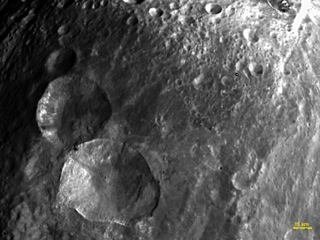 "In this image, obtained by the framing camera on NASA's Dawn spacecraft, a set of three craters, informally nicknamed ""Snowman"" by the camera's team members, is located in the northern hemisphere of Vesta."