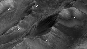 The white arrows point out the seasonal dark streaks, called recurring slope lineae (RSL), on the surface of Mars. The Valles Marineris region has the densest population of streaks on the Red Planet. NASA / JPL-Caltech / University of Arizona